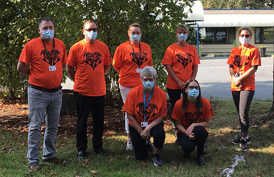Seven Providence Living staff members wearing orange shirts